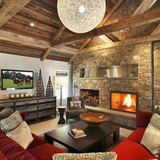 Réalisation d'un salon design de taille moyenne et ouvert avec un manteau de cheminée en pierre, un mur multicolore, un sol en bois brun, une cheminée standard et un téléviseur fixé au mur.