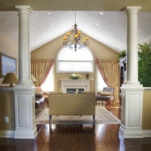 Diseño de salón para visitas cerrado, tradicional, grande, sin televisor, con paredes beige, suelo de madera en tonos medios, chimenea tradicional, marco de chimenea de metal y suelo marrón