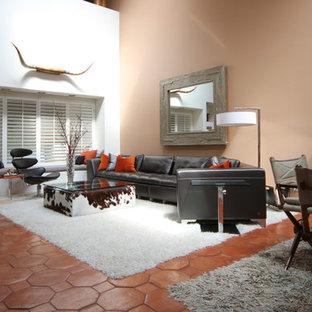 Diseño de salón para visitas abierto, moderno, grande, sin chimenea y televisor, con parades naranjas y suelo de baldosas de terracota