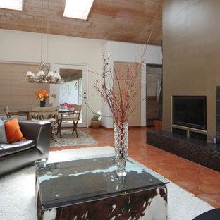 Modelo de salón para visitas abierto, minimalista, grande, con parades naranjas, suelo de baldosas de terracota, todas las chimeneas, marco de chimenea de baldosas y/o azulejos y pared multimedia