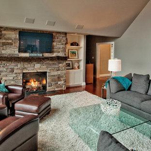 Inspiration för ett eklektiskt vardagsrum, med en spiselkrans i sten, en väggmonterad TV, grå väggar, mörkt trägolv och en standard öppen spis