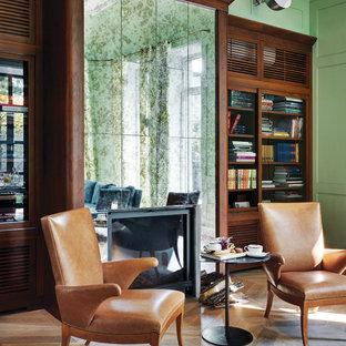 Стильный дизайн: гостиная комната в стиле современная классика с библиотекой, зелеными стенами, паркетным полом среднего тона и стандартным камином - последний тренд