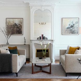 Cette photo montre un salon chic fermé avec un mur blanc, un sol en bois foncé, une cheminée standard, un manteau de cheminée en pierre, une salle de réception et un sol marron.