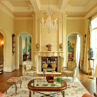 Immagine di un soggiorno mediterraneo con sala formale, pareti beige, pavimento in legno massello medio, camino bifacciale, cornice del camino in pietra e nessuna TV