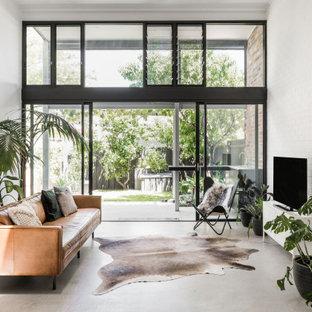 Idee per un soggiorno contemporaneo aperto con pareti bianche, pavimento in cemento, TV autoportante e pareti in mattoni