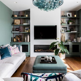 Photo of a contemporary living room in Other with green walls, medium hardwood flooring, a ribbon fireplace, a wall mounted tv and brown floors.