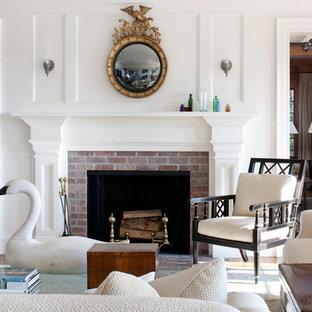 Idee per un grande soggiorno tradizionale aperto con sala formale, pareti bianche, pavimento in legno massello medio, camino classico e cornice del camino in mattoni
