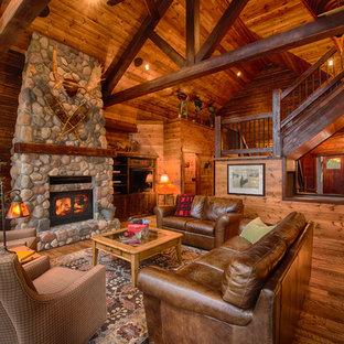 ミネアポリスのラスティックスタイルのおしゃれなLDK (茶色い壁、無垢フローリング、標準型暖炉、石材の暖炉まわり、埋込式メディアウォール) の写真