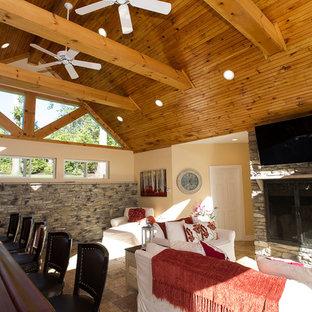 Idee per un soggiorno stile rurale di medie dimensioni e chiuso con angolo bar, pareti beige, pavimento in travertino, camino classico, cornice del camino in pietra, TV a parete e pavimento beige
