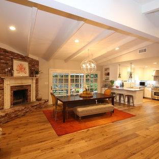 Modelo de salón con barra de bar abierto, minimalista, extra grande, sin televisor, con paredes beige, suelo de madera en tonos medios, chimenea de esquina y marco de chimenea de ladrillo