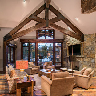 Photo of a country open concept living room in Denver with dark hardwood floors, a standard fireplace, a stone fireplace surround and a wall-mounted tv.