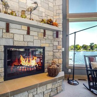 グランドラピッズの大きいおしゃれなLDK (フォーマル、マルチカラーの壁、カーペット敷き、標準型暖炉、石材の暖炉まわり、埋込式メディアウォール、ベージュの床) の写真