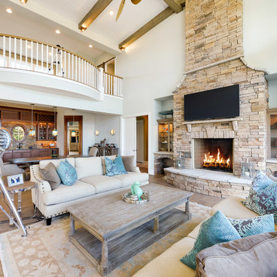 Example of a beach style open concept medium tone wood floor living room design in Other with a stone fireplace, a wall-mounted tv, a standard fireplace and white walls