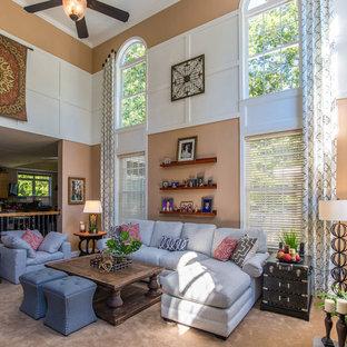 Foto di un grande soggiorno tradizionale aperto con pareti beige, moquette, camino classico, cornice del camino in pietra e TV a parete
