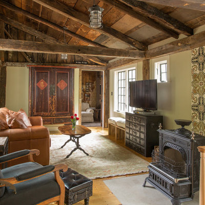 Inspiration for a large cottage medium tone wood floor living room remodel in Boston with green walls, a wood stove and a tv stand