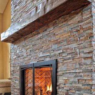 ニューヨークの大きいトラディショナルスタイルのおしゃれなLDK (フォーマル、黄色い壁、無垢フローリング、吊り下げ式暖炉、石材の暖炉まわり、茶色い床) の写真