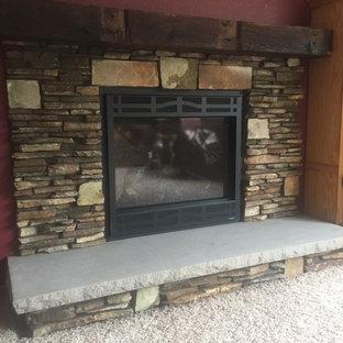 シーダーラピッズの中サイズのラスティックスタイルのおしゃれなリビング (標準型暖炉、石材の暖炉まわり、赤い壁、カーペット敷き、ベージュの床) の写真