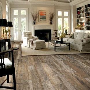Ejemplo de salón para visitas abierto, rural, de tamaño medio, con paredes beige, suelo de madera en tonos medios, chimenea tradicional, marco de chimenea de yeso y suelo marrón