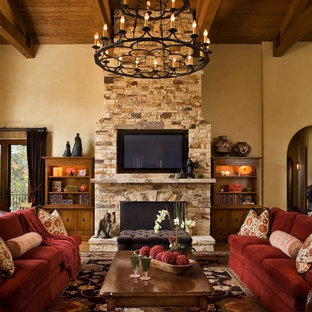 Living room - rustic living room idea in Other with a stone fireplace