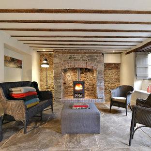 Idee per un piccolo soggiorno country aperto con pareti bianche, stufa a legna, cornice del camino in mattoni e pavimento in pietra calcarea