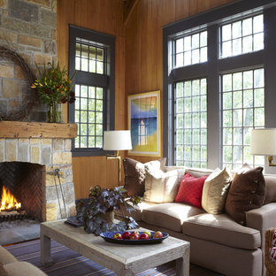 Example of a mountain style living room design in Birmingham with a standard fireplace, a stone fireplace and no tv