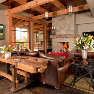 Example of a mountain style concrete floor living room design in Other with gray walls