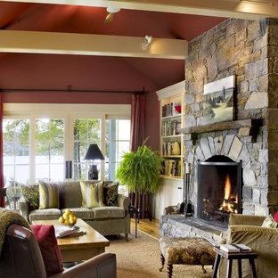 Idéer för ett rustikt vardagsrum, med röda väggar och en spiselkrans i sten
