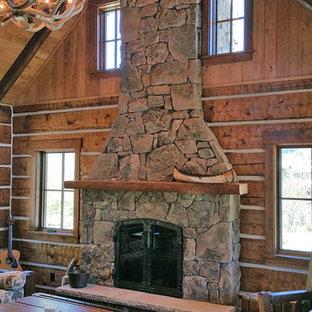 Esempio di un piccolo soggiorno rustico stile loft con pareti marroni, parquet scuro, camino classico, cornice del camino in pietra e nessuna TV