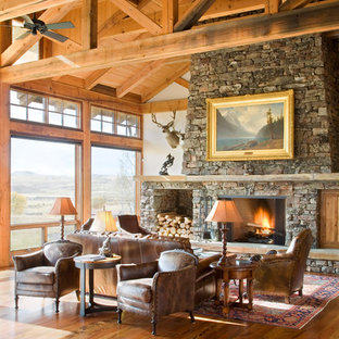 Mid-sized mountain style formal and open concept medium tone wood floor living room photo in Other with white walls, a standard fireplace and a stone fireplace