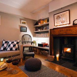Rustik inredning av ett mellanstort separat vardagsrum, med ett bibliotek, beige väggar, ljust trägolv, en öppen vedspis och en spiselkrans i trä