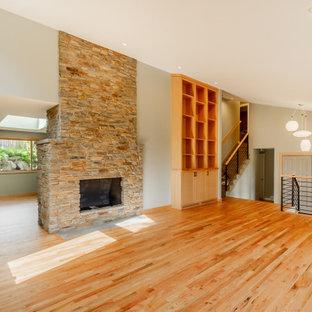 Foto de salón abierto, moderno, con paredes grises, suelo de madera en tonos medios, marco de chimenea de piedra y suelo naranja