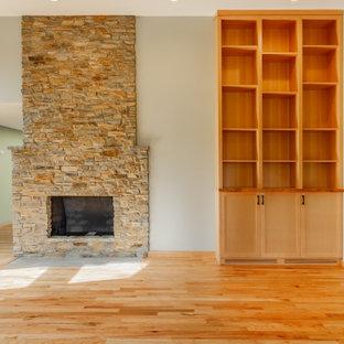 シアトルのモダンスタイルのおしゃれなLDK (グレーの壁、無垢フローリング、石材の暖炉まわり、オレンジの床) の写真