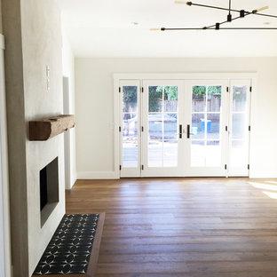 サンタバーバラの中サイズのインダストリアルスタイルのおしゃれなLDK (白い壁、両方向型暖炉、コンクリートの暖炉まわり、無垢フローリング) の写真
