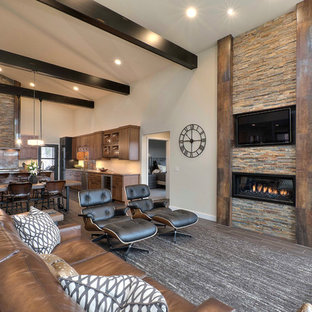 Example of a mountain style formal and open concept living room design in Other with beige walls, a ribbon fireplace, a stone fireplace and a wall-mounted tv