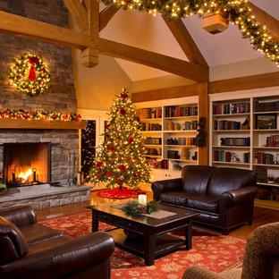 Cette photo montre un très grand salon avec une bibliothèque ou un coin lecture chic ouvert avec une cheminée standard, un manteau de cheminée en pierre, un mur beige et un sol en bois brun.