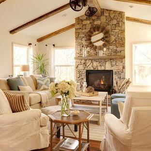 Modelo de salón para visitas marinero con paredes blancas, suelo de madera oscura, chimenea tradicional y marco de chimenea de piedra