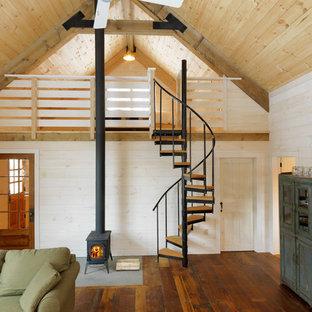 Esempio di un piccolo soggiorno stile rurale con stufa a legna, pareti beige e pavimento in legno massello medio