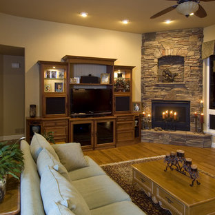 Inspiration for a mid-sized timeless open concept medium tone wood floor living room remodel in Denver with beige walls, a corner fireplace, a stone fireplace and a media wall