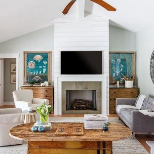 ジャクソンビルのビーチスタイルのおしゃれなリビング (グレーの壁、淡色無垢フローリング、標準型暖炉、壁掛け型テレビ) の写真