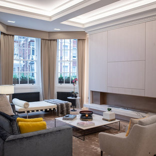 Photo of a contemporary open plan living room in London with a stone fireplace surround, a concealed tv, grey walls, medium hardwood flooring, a ribbon fireplace and brown floors.