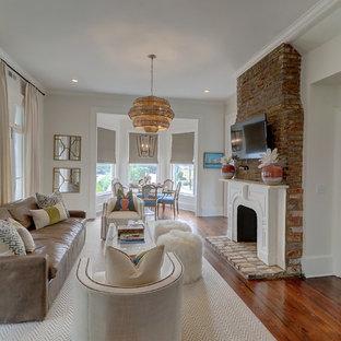Exempel på ett klassiskt separat vardagsrum, med vita väggar, mörkt trägolv, en standard öppen spis, en spiselkrans i gips, en väggmonterad TV och brunt golv