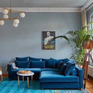 Stilmix Wohnzimmer mit blauer Wandfarbe, braunem Holzboden und braunem Boden in Sonstige