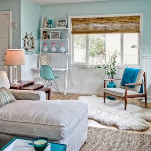 Example of a coastal open concept medium tone wood floor living room design in San Luis Obispo with blue walls