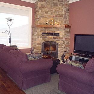 Diseño de salón abierto, contemporáneo, de tamaño medio, con paredes rosas, suelo de madera oscura, chimenea de esquina, marco de chimenea de piedra y televisor independiente