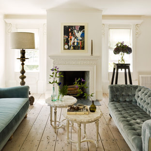 Design ideas for a mid-sized traditional formal enclosed living room in New York with white walls, light hardwood floors, a standard fireplace, a plaster fireplace surround, beige floor and no tv.