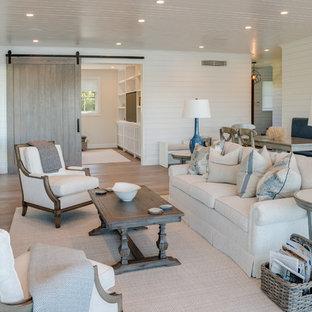 ニューヨークのビーチスタイルのおしゃれなLDK (白い壁、淡色無垢フローリング、横長型暖炉、石材の暖炉まわり、壁掛け型テレビ、ベージュの床) の写真
