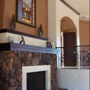 フェニックスのサンタフェスタイルのおしゃれなリビング (マルチカラーの壁、磁器タイルの床、標準型暖炉、石材の暖炉まわり、ベージュの床) の写真