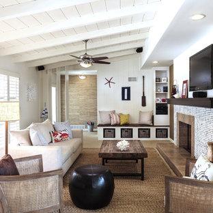 Modelo de salón abierto, costero, de tamaño medio, con chimenea tradicional, televisor colgado en la pared, paredes multicolor y moqueta