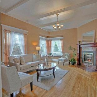 他の地域の中くらいのヴィクトリアン調のおしゃれな独立型リビング (フォーマル、オレンジの壁、淡色無垢フローリング、コーナー設置型暖炉、石材の暖炉まわり、テレビなし) の写真