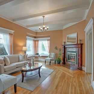 他の地域の中サイズのヴィクトリアン調のおしゃれな独立型リビング (フォーマル、オレンジの壁、淡色無垢フローリング、コーナー設置型暖炉、石材の暖炉まわり、テレビなし) の写真